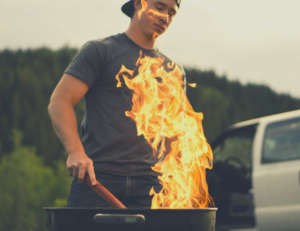 man creating fire on grill