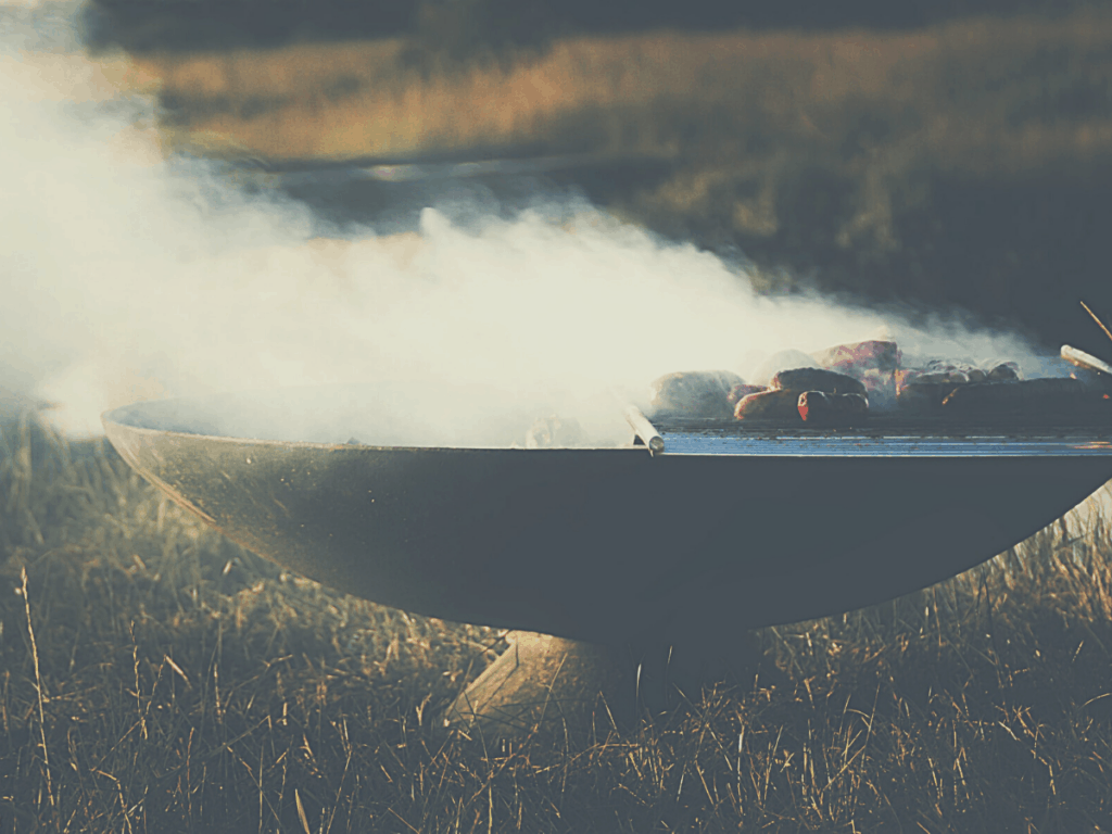 smoking meat on a portable smoker in a field