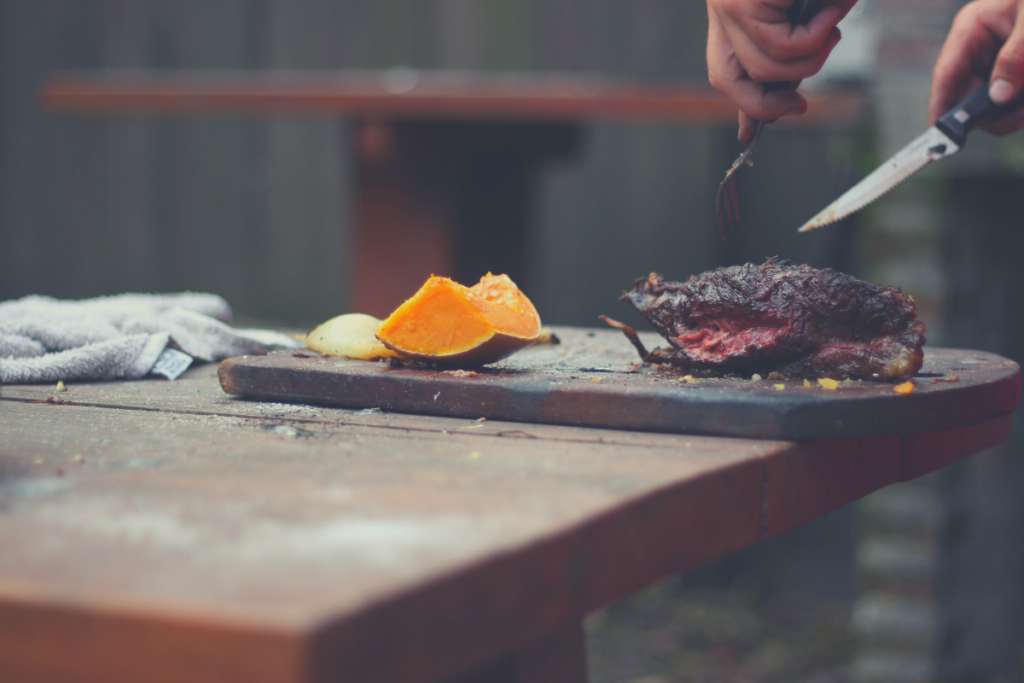 man cutting smoked meat with fruit