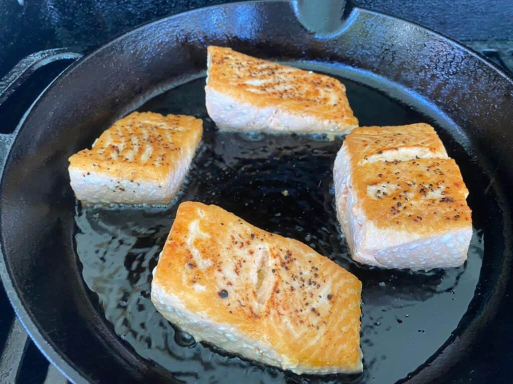 Salmon cooking in a cast iron skillet